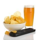 Geïsoleerdee chips, bier en afstandsbediening stock foto