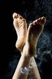 Geïsoleerdep vrouwelijke voeten op zwarte die achtergrond door blauwe rook wordt omringd Royalty-vrije Stock Foto