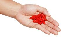 Geïsoleerdes hand met rode geneeskunde Stock Foto's