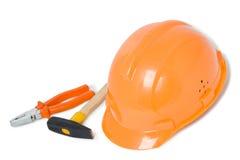 Geïsoleerdet oranje helm, buigtang en hamer royalty-vrije stock afbeelding