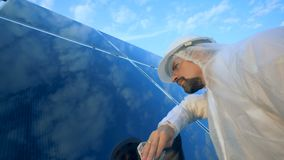 Geïsoleerdk op witte teruggegeven background De geconcentreerde inspecteur poetst een zonnemodule op stock video