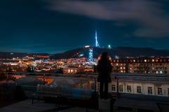 Geórgia, Tbilisi - 05 02 2019 - Opinião da arquitetura da cidade da noite com posição humana da silhueta no telhado Os marcos fam imagens de stock