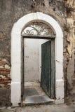 Geöffnete alte verwitterte Tür auf einer zerbröckelnden Wand Stockfoto