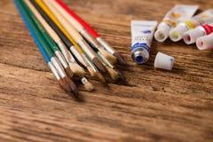 Geöffnete blaue Acrylfarbe und Satz Malerpinsel Stockbilder