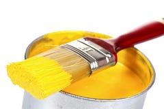 Geöffnete Dose des gelben Lackes und des Pinsels lizenzfreies stockbild