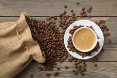 Geöffnete Kaffeetasche mit Bohnen und weißer Schale coffe Stockbild