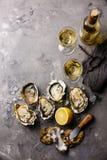 Geöffnete Oysters Fines de Claire und Weißwein lizenzfreie stockfotografie