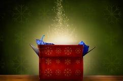 Geöffnete Weihnachtsgeschenkbox mit Glühen und funkelnden Sternen Stockfoto