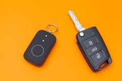 Geöffneter Auto-Schlüssel mit Fernbedienung auf einem orange Hintergrund, Draufsicht lizenzfreies stockfoto