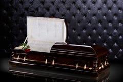 Geöffneter hölzerner brauner Sarkophag mit rote Rosen auf grauem Luxushintergrund Schatulle, Sarg auf königlichem Hintergrund Lizenzfreie Stockbilder