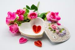 Geöffneter Herzkasten mit Mini handcraft Innere mit Dekorationsblumenstrauß von Rosen auf weißem Hintergrund lizenzfreie stockbilder