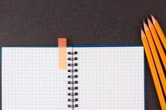 Geöffneter Notizblock und bunte Bleistifte auf schwarzem Hintergrund Stockfoto