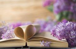 Geöffnetes Buch auf dem Tisch mit Seiten mögen Herz und Blumen Stockbild