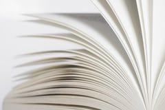 Geöffnetes Buch auf weißem Hintergrund Stockbilder