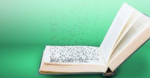 Geöffnetes Buch mit fallenden Buchstaben auf grünem Hintergrund Stockfotografie