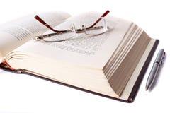 Geöffnetes Buch mit Gläsern und Feder stockfotografie