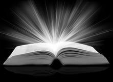 Geöffnetes Buch mit Strahlen der Leuchte Stockfoto