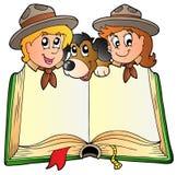 Geöffnetes Buch mit zwei Pfadfindern und Hund Stockfotos