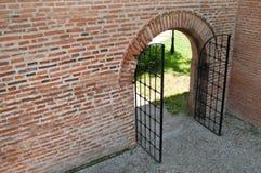 Geöffnetes Eisen schmiedete Gatter mit Backsteinmauer Stockfotografie