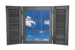 Geöffnetes hölzernes Fenster zur Ansicht des blauen Himmels lokalisiert auf weißem Backg Lizenzfreie Stockfotos