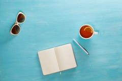 Geöffnetes Notizbuch mit Stift, Tasse Tee und Sonnenbrille auf blauem Holztisch Beschneidungspfad eingeschlossen Schreiben, blogg Lizenzfreie Stockfotografie