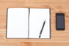 Geöffnetes Notizbuch oder Notizblock mit Feder auf hölzernem Schreibtisch Lizenzfreie Stockfotografie