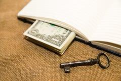 Geöffnetes Notizbuch, Schlüssel und Geld auf dem alten Gewebe Stockbilder