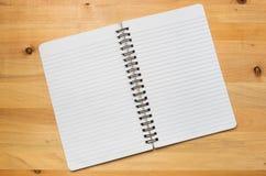 Geöffnetes Notizbuch showin seine gestreiften Blätter über Holztischspitze lizenzfreie abbildung