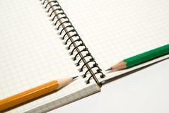 Geöffnetes Notizbuch und Bleistifte an über Weiß Lizenzfreie Stockfotografie