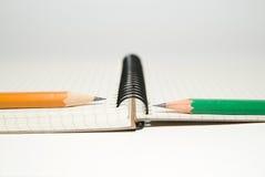 Geöffnetes Notizbuch und Bleistifte an über Weiß Stockfotos