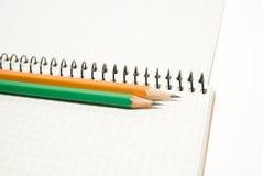 Geöffnetes Notizbuch und Bleistifte an über Weiß Stockbild
