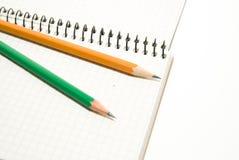 Geöffnetes Notizbuch und Bleistifte an über Weiß Lizenzfreie Stockbilder