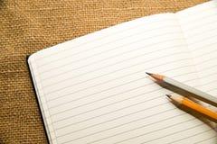 Geöffnetes Notizbuch und Bleistifte auf dem alten Gewebe Stockbild