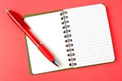 Geöffnetes Notizbuch und rote Feder Stockbild