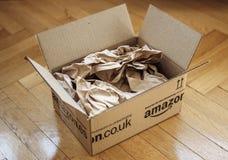 Geöffnetes Paket von Amazonas auf Hauptparkettboden Stockbilder