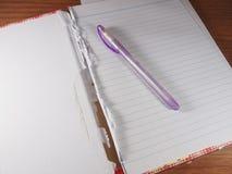 Geöffnetes und heftiges Notizbuch mit Kugelschreiber-blauer Tinte Lizenzfreies Stockfoto