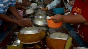 Ge allmosa av ris till en buddistisk munk i tempel arkivfilmer