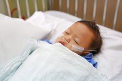 ?ge de b?b? gar?on au sujet du sommeil de 1 an sur le lit patient avec obtenir l'oxyg?ne par l'interm?diaire des fourches nasales photos libres de droits