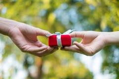 Ge den röda gåvaasken in med händer på speciala dagar för special person, på gräsbakgrund Vigselringask royaltyfria bilder