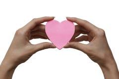 Ge förälskelsebegrepp med räcker innehav en rosa hjärta. Arkivbilder