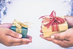 Ge gåvaasken in med händer på speciala dagar för special person- och kopieringsutrymmebakgrund royaltyfri fotografi