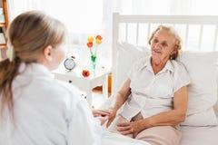 Ge omsorg för åldring Doktor som besöker äldre tålmodigt hemmastatt Arkivbilder