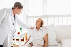 Ge omsorg för åldring Doktor som besöker äldre tålmodigt hemmastatt Arkivfoton