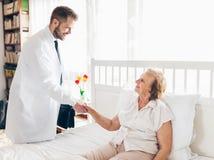 Ge omsorg för åldring Doktor som besöker äldre tålmodigt hemmastatt Arkivfoto