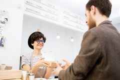 Ge pappersasken med sötsaker till kunden i bagare shoppa royaltyfria bilder