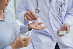 Ge preventivpillerar till patienten arkivbild