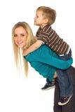 ge rittsonen för moder på ryggen Arkivbilder