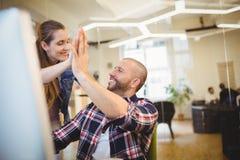 Ge sig för affärsman som är högt-fem till den kvinnliga kollegan i regeringsställning Fotografering för Bildbyråer