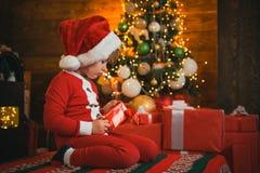 Ge?soleerd op witte achtergrond Vrolijk de stemmingsspel van het jongens leuk kind dichtbij Kerstmisboom Vrolijke en heldere Kers royalty-vrije stock afbeeldingen
