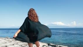 Ge?soleerd over witte achtergrond Het meisje kijkt op oceaan, zwarte uniformjas, haaropwinding in wind, langzame motie stock videobeelden